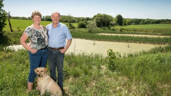 """Ole Lyngby Pedersen fra Odder kan onsdag vinde """"Baltic Farmer of the year""""-prisen. Her ses han sammen med hustroen Hanne og deres hund."""