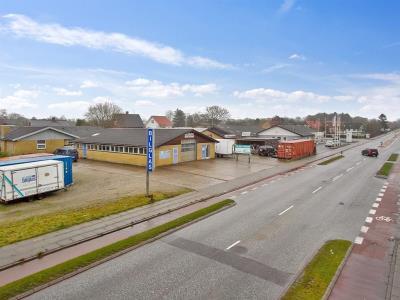 Velbeliggende erhvervsejendom med 3 værkstedshaller og 2 boliglejemål